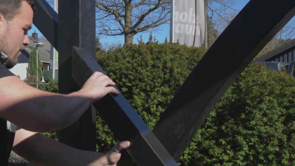 Ein Pfosten wird an einem Carport befestigt